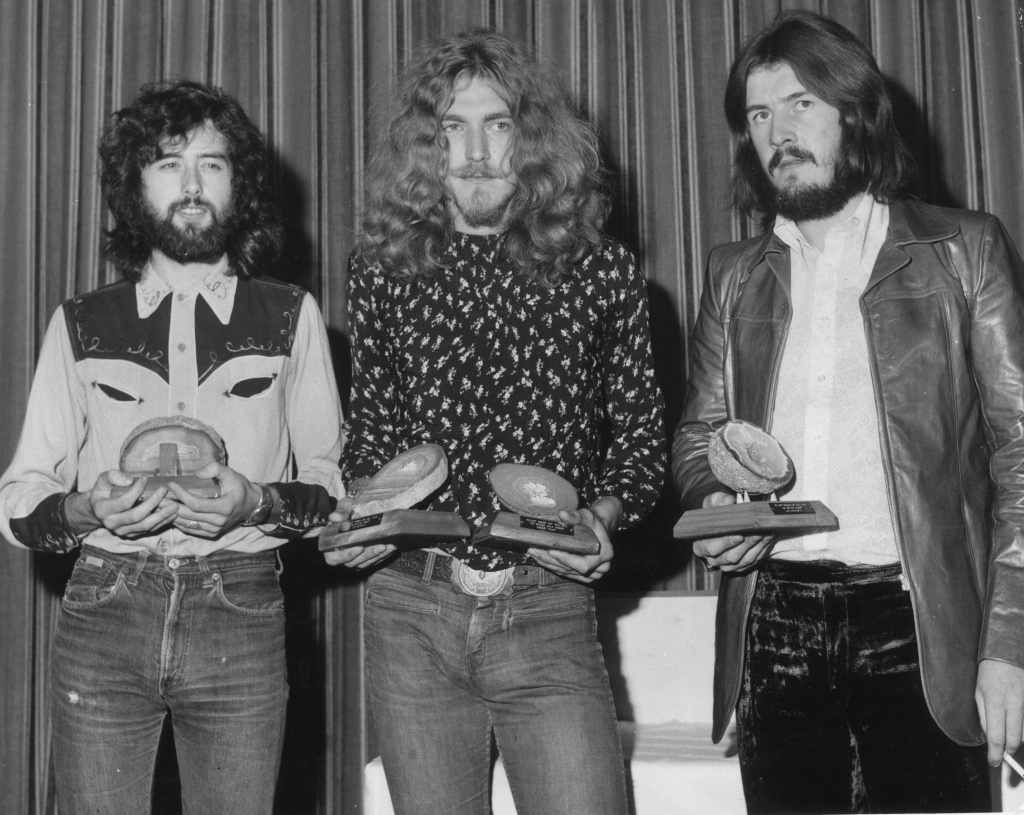16th September 1970:  British rock band Led Zeppelin collect their geode awards after being voted top British group in the Melody Maker Pop Poll in London. From left to right, they are Jimmy Page, Robert Plant (who also won the Best British Singer award), and John Bonham.  (Photo by Roger Jackson/Central Press/Getty Images)