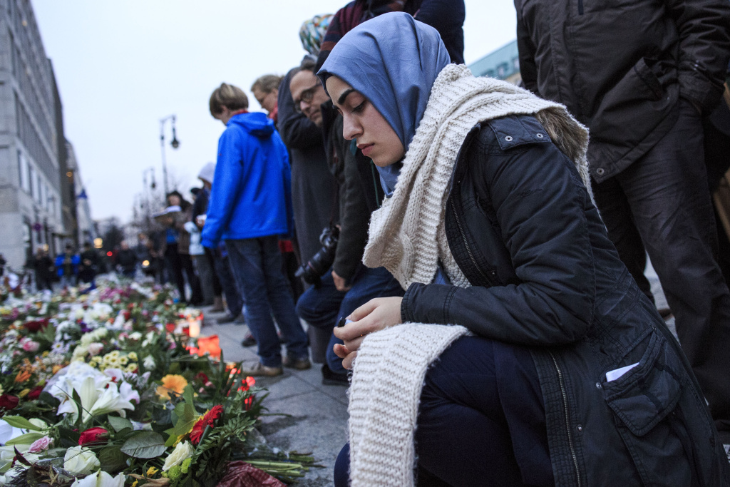 A young Muslim woman squats outside the French Embassy among candles, messages and flowers left by mourners commemorating the victims of last Friday's terrorist attacks in Paris.
