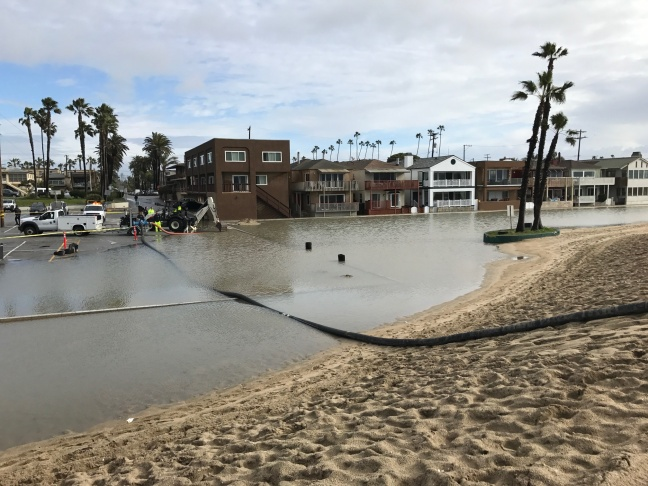 The City of Seal Beach was pumping water Monday morning from a large pool of rainwater that had built up south of the Seal Beach pier between the sand berm and a row of homes along the beach.