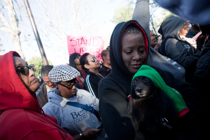 La Martini Sterling and her dog Sandra Falls listen to speakers at the Trayvon Martin rally in Leimert Park.