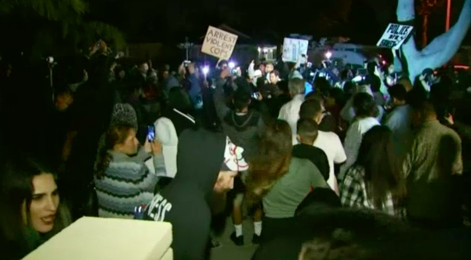 In this file photo taken from a screenshot of TV news footage, protesters are seen clashing with police outside a home where an off-duty Los Angeles policeman fired a single round during an off-duty tussle with a 13-year-old boy in Anaheim.
