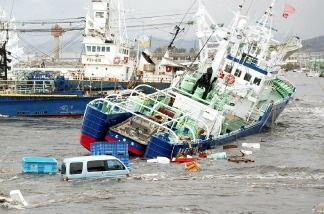 Fishing boats and vehicles are carried by a tsunami wave at Onahama port in Iwaki city, in Fukushima prefecture, northern Japan on March 11, 2011.