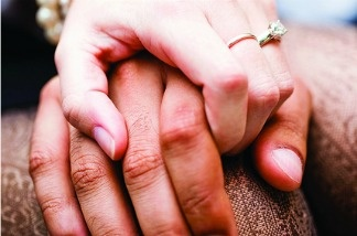 A mixed-race couple holds hands.