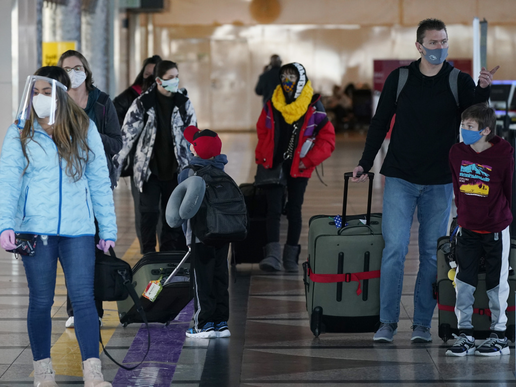 Travelers wear face masks in the main terminal of Denver International Airport on Dec. 31, 2020. Starting Feb. 1, travelers will be required to wear face masks on nearly all forms of public transportation.