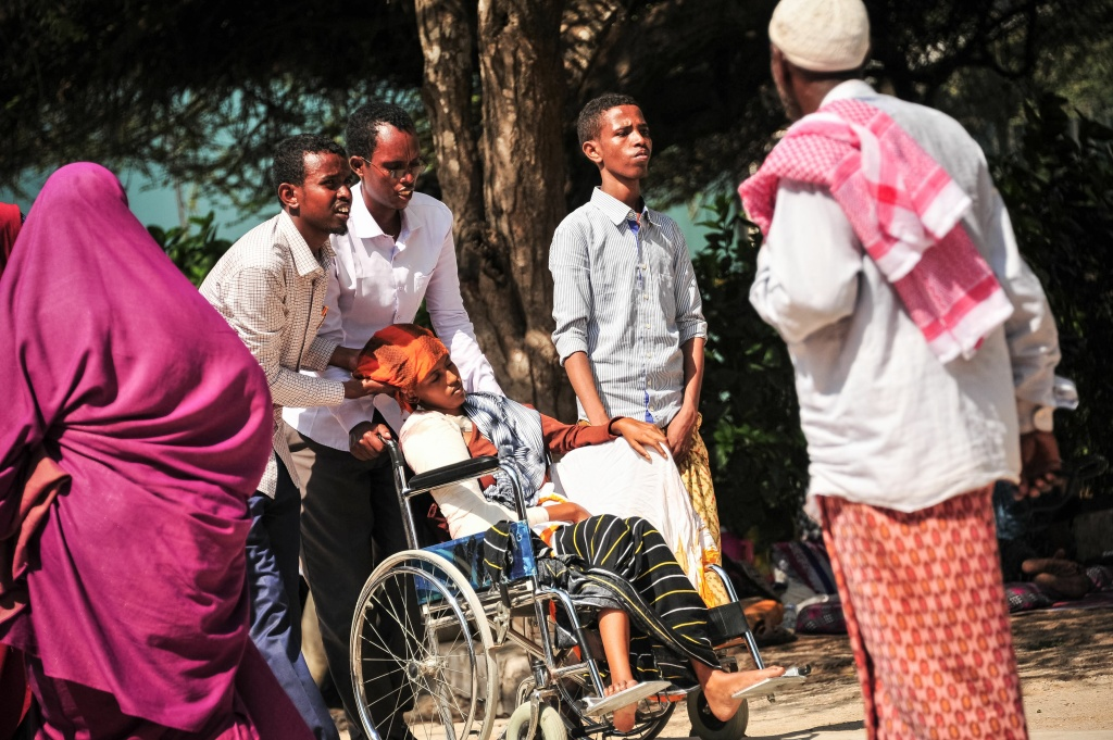 People pull in a woman a wheelchair. She was injured when a truck bomb exploded in the center of Mogadishu on October 15, 2017.