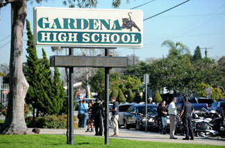 People walk past the entrance to Gardena High School in Gardena, California January 18, 2011 after two students were shot, one in the head, when a gun went off accidentally in a classroom.