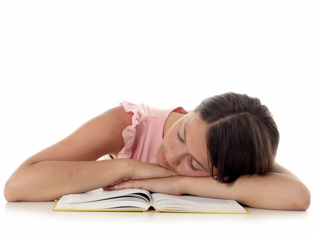 A stock photo of a woman sleeping on a text book.