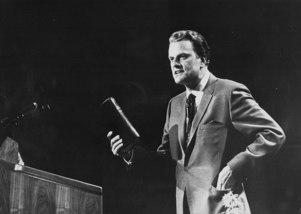 American evangelist Billy Graham, giving a speech on stage, circa 1970.