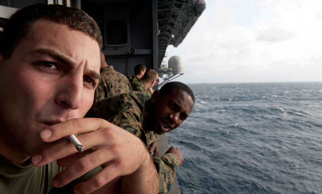 US Marine Lance Cpl. Joseph Lipton, from Summers, CT, takes a cigarette break on the side of the USS Wasp(LHD-1) Februariy 5, 2012, during Operation Bold Alligator 2012, a multinational military exercise involving 14,000 Marines, Sailors, Airmen, and Soldiers with more than 25 ships and 8 countries.