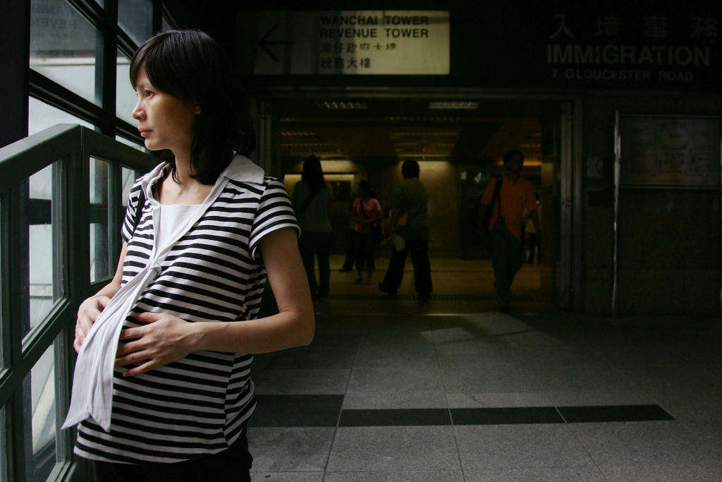 A pregnant woman stands in front of the entrance of Hong Kong Immigration Department on June 29, 2007 in Hong Kong, China.