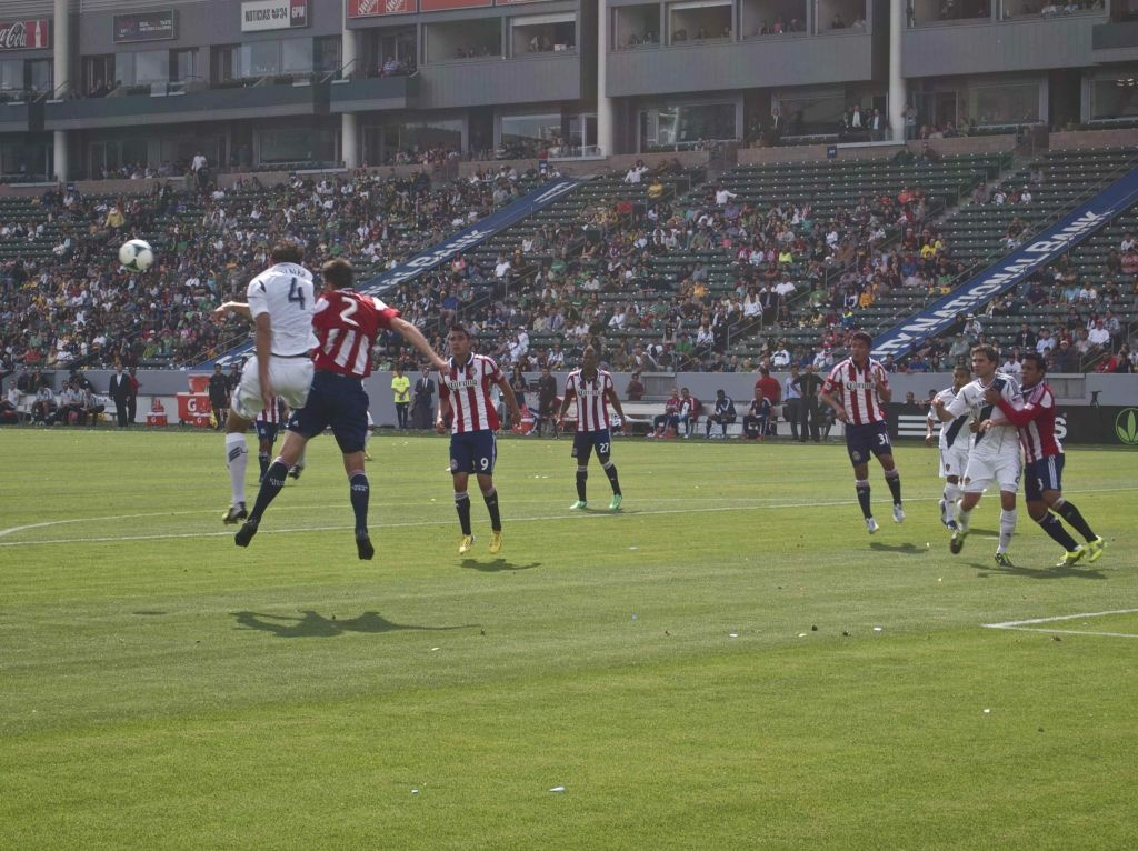 Chivas USA players, in red-and-white-striped jerseys, battle the L.A. Galaxy in March 2013. Two former coaches with the Chivas USA youth academy have filed a lawsuit, claimng the organization discriminated against them for not being Latino. The soccer organization has issued a statement saying it respects diversity.