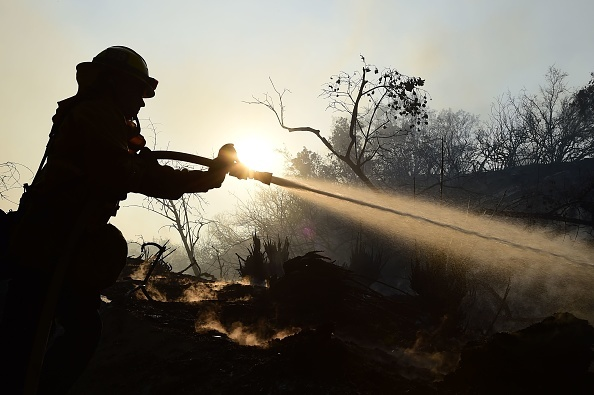 LAFD Firefighter Allen Janzen puts down smoldering embers in the Bel Air neighborhood of Los Angeles while fighting the Skirball Fire on December 6, 2017.