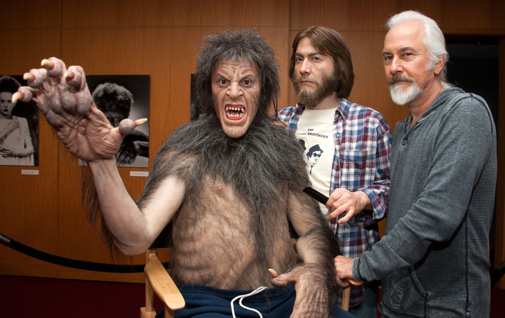 Rick Baker helps Michael Jackson fit teeth into his special makeup appliance.
