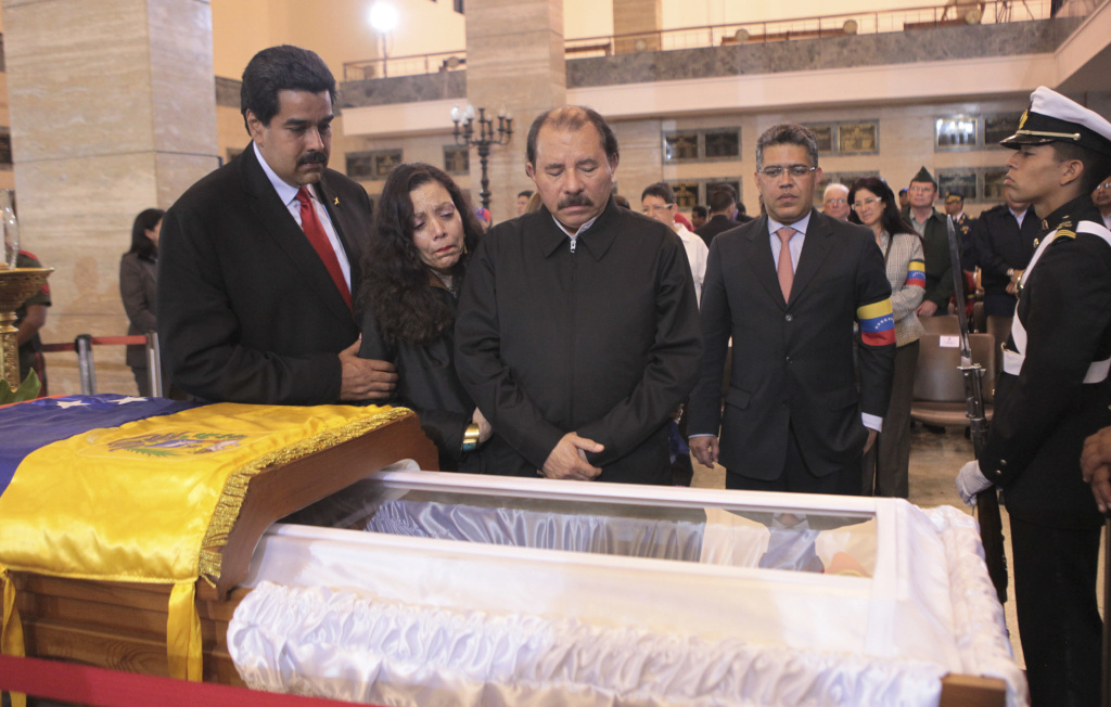 In this photo released by Miraflores Press Office, Nicolas Maduro, Venezuela's acting president, left, Nicaragua's President Daniel Ortega, third from left, and his wife Rosa Murillo, second from left, mourn next to the coffin containing the remains of Venezuela's late President Hugo Chavez during his wake at a military academy.