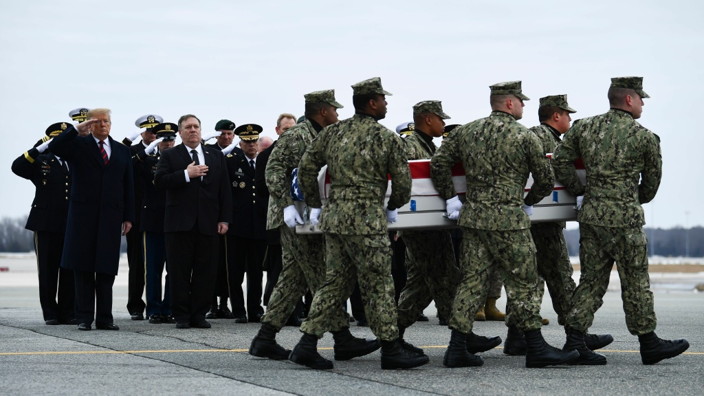 As President Donald Trump and Secretary of State Mike Pompeo watch, a U.S. Navy team moves a transfer case containing the remains of Scott A. Wirtz, Saturday at Dover Air Force Base.