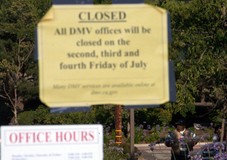 A California Department of Motor Vehicles customer looks at a closed sign posted on the door of a DMV branch July 10, 2009 in Corte Madera, California.