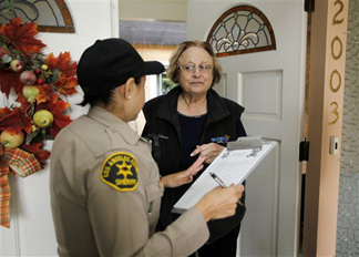Robin Gehr, 77, talks with Los Angeles County Sheriff's Deputy Gonzalez, saying she has no plans to leave her hillside home, as a storm heads for California, renewing concern over mudslides in the area beneath last year's Station wildfire, in La Canada-Flintridge, Calif., Friday, Feb. 19, 2010.