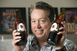 Cal Poly Pomona professor Owen Williams with bottles of Bronco Brown brewed with the help of university students