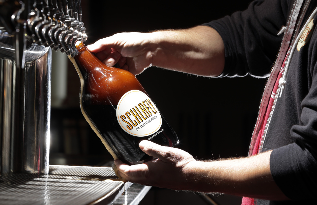 In this photo made Friday, March 27, 2015, an employee demonstrates for a photograph the pouring of a growler of beer at Schlafly Tap Room in St. Louis. As the craft beer industry grows, so are options for learning to brew. More colleges are now introducing degree programs to teach the art and science of beer-making.