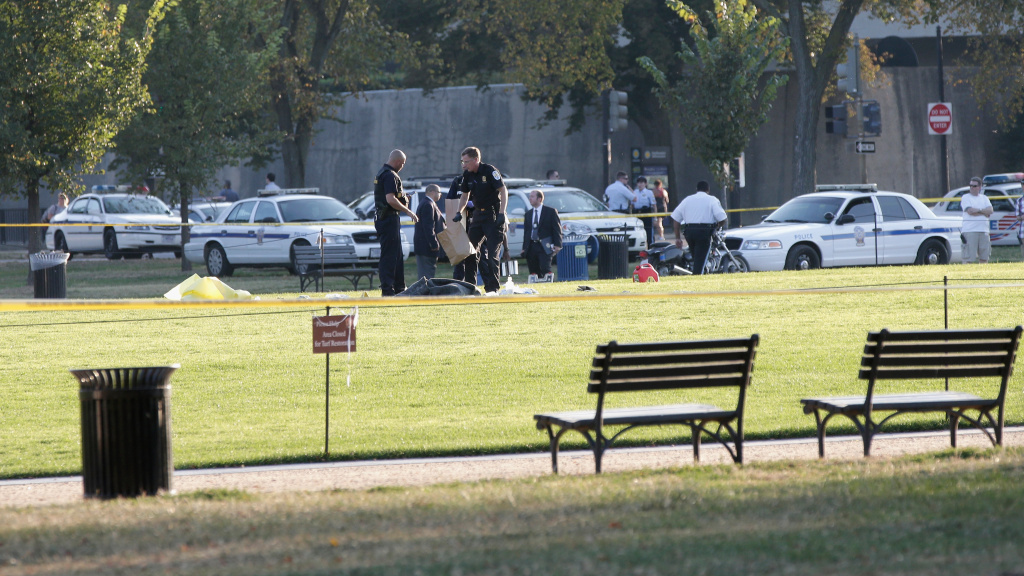 Police investigate the scene after a man set himself ablaze on the National Mall's lawn Friday afternoon in Washington, DC. The man did not survive his injuries, according to reports.