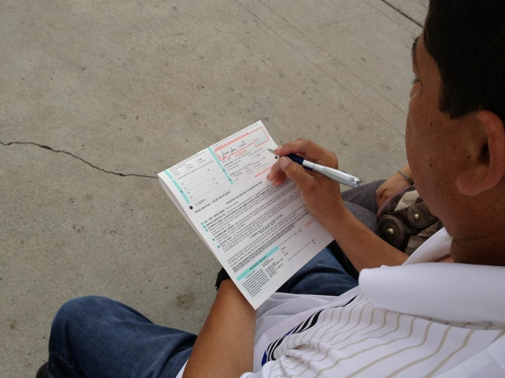 In this file photo, an eligible voter fills out a form outside  St. Joseph's Catholic church in Hawthorne, where parishioners set up a registration table. Monday, October 20, 2014 is the last day to register to vote.
