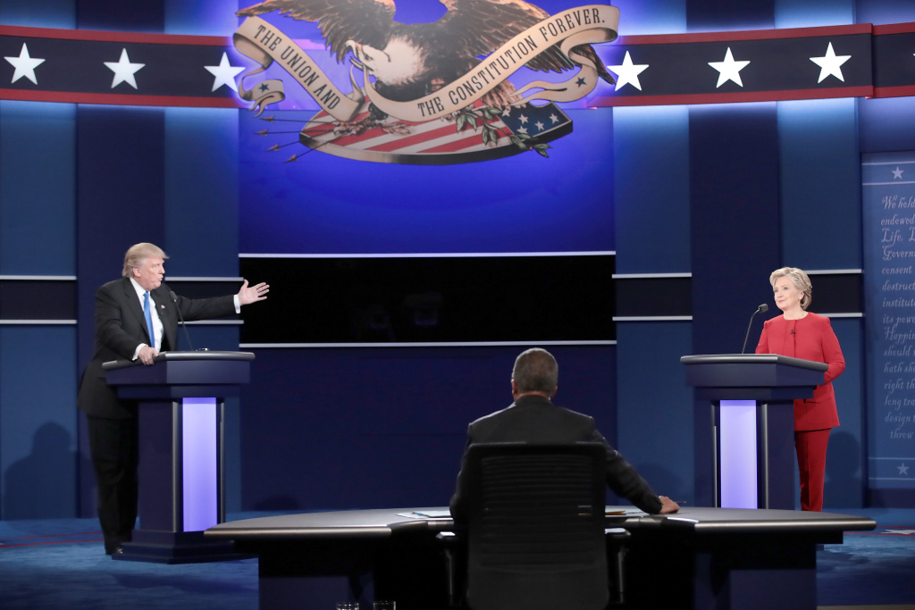 Republican presidential nominee Donald Trump (L) speaks as Democratic presidential nominee Hillary Clinton and Moderator Lester Holt listen during the Presidential Debate at Hofstra University.