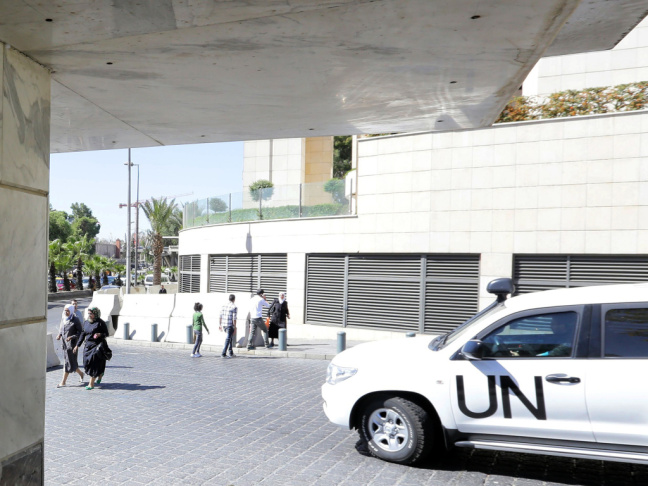 A United Nations vehicle carrying inspectors from the Organization for the Prohibition of Chemical Weapons (OPCW) leaves a hotel in Damascus, on Wednesday. Some 19 OPCW arms experts are in Syria and have started to destroy weapons production facilities.