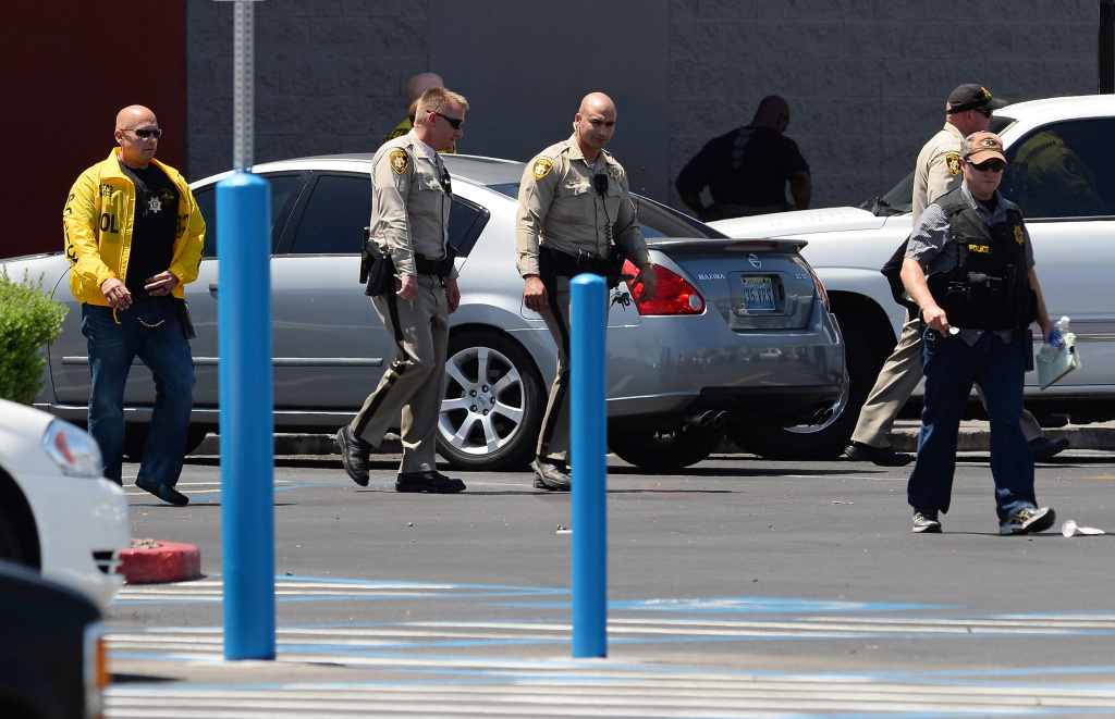 Las Vegas Metropolitan Police Department officers walk outside a Wal-Mart on June 8, 2014 in Las Vegas, Nevada. Two officers were reported shot and killed by two assailants at a pizza restaurant near the Wal-mart. The two suspects then reportedly went into the Wal-Mart where they killed a third person before killing themselves.