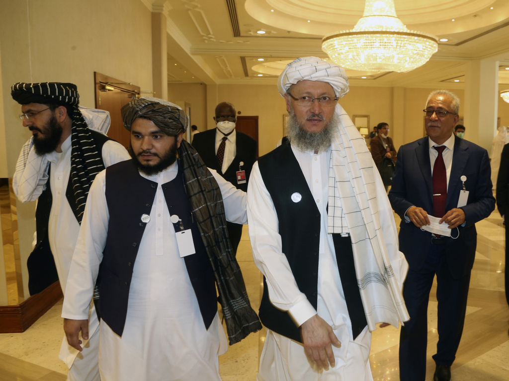 Abdul Salam Hanafi (right), a member of the Taliban negotiating team, heads to the opening session of peace talks between the Afghan government and the Taliban in Doha, Qatar, on Saturday.