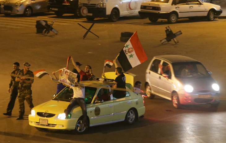 Syrians celebrate in a street in Damascus after Syrian President Bashar al-Assad was announced as the winner of the country's presidential elections.
