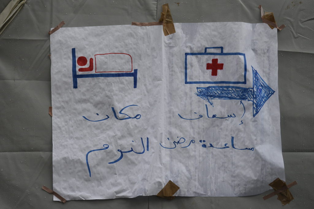 Pictograms and arab writing on a makeshift sign show the way to a rest area and medical treatment