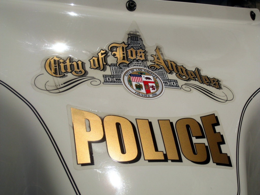 The logo for the LAPD appears on the front of a police motorcycle
