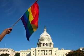 A demonstrator waves a rainbow flag in front of the US Capitol in Washington D.C.