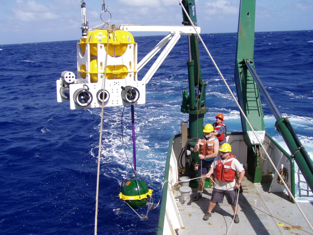 Scripps workers deploy a seismometer (green) and a unit to record and charge the instrument (yellow) offshore in 2006. The sensor will measure undersea ground shaking and record data until the team returns to retrieve it.