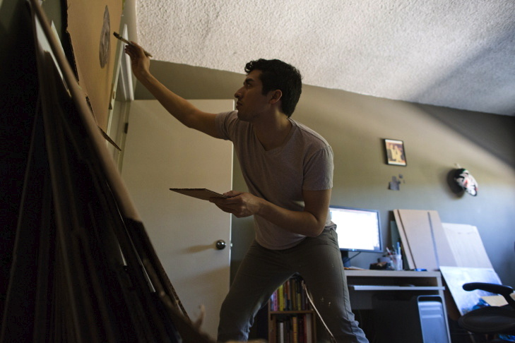Ramiro Gomez paints in a spare bedroom that he uses as a studio in his West Hollywood apartment.