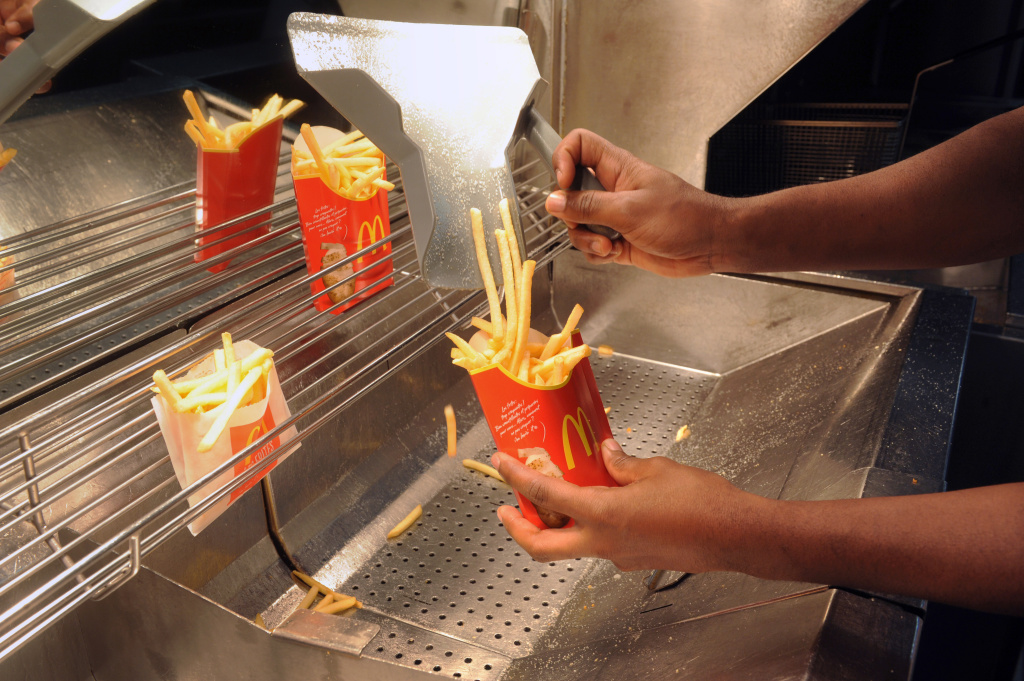 An employee serves French fries at a US