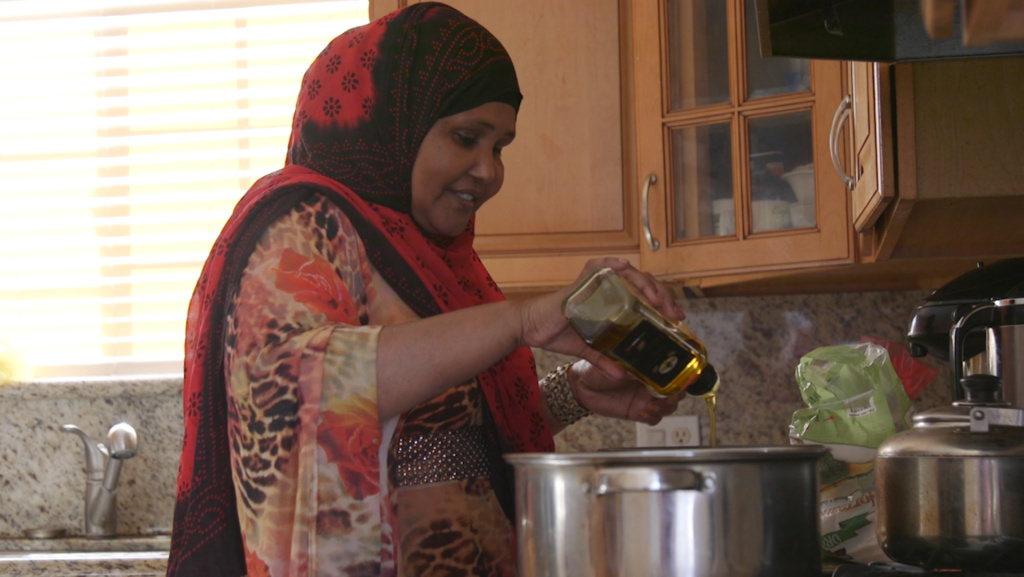 Mariam Ali, a Somali refugee who lives in San Diego's Teralta neighborhood, pours olive oil into a pot for alfredo sauce, Feb. 26, 2016.