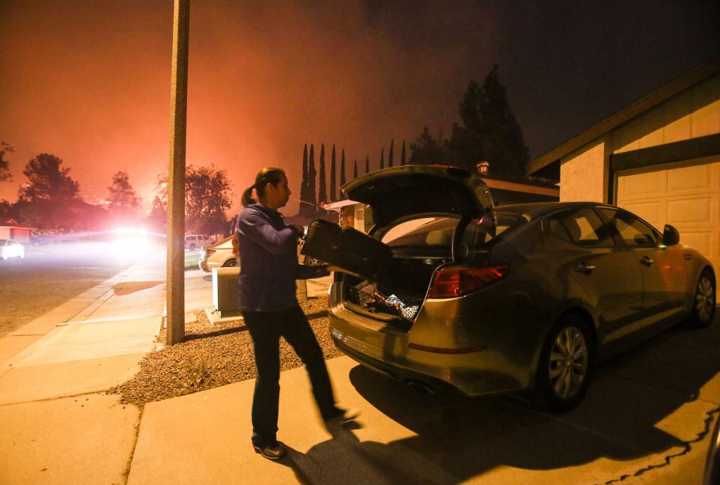 A woman evacuates her home as a wildfire burns along a hillside near homes in Santa Paula, California, on December 5, 2017.