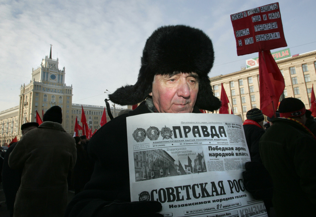A Russian Communist Party supporter holds pro-communist newspapers