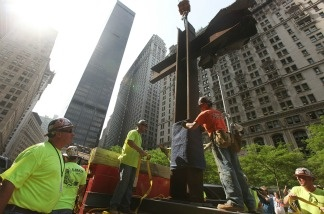 Workers prepare the World Trade Center cross to be moved into its permanent home at the 9/11 Memorial Museum after a blessing ceremony on July 23, 2011 in New York City.