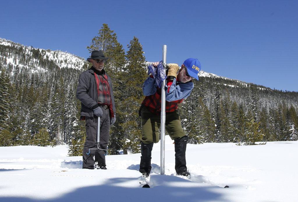 Frank Gehrke, right, chief of the California Cooperative Snow Surveys Program for the Department of Water Resources, plunges the survey tube into the snowpack as he conducts the third manual snow survey of the season at Phillips Station, Wednesday, March 1, 2017, near Echo Summit, Calif.