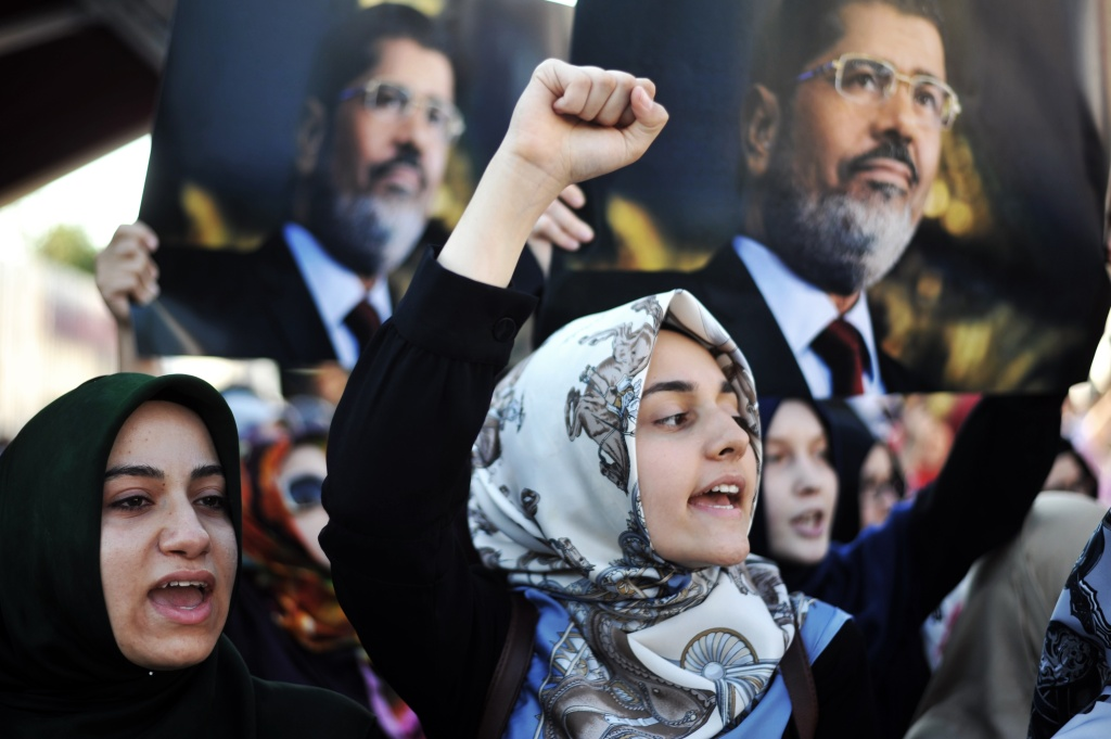 Turkish Islamist women protesters chants slogans as they hold posters of ousted Egyptian President Mohamed Morsi during a pro-Morsi demonstration in front of the Fatih Mosque in Istanbul, on July 8, 2013.
