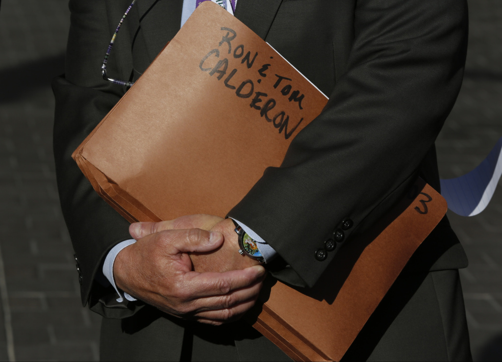 File: Department of Justice Public Affairs Officer Thom Mrozek holds a folder tagged with the names of California State Sen. Ron Calderon and his brother Tom Calderon, during a news conference outside the Edward R. Royal Federal Court building in Los Angeles, Monday, Feb. 24, 2014.