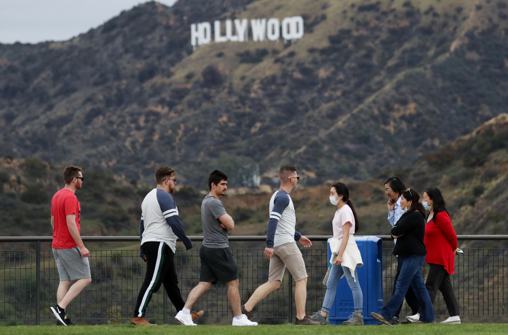 People, some wearing face masks, walk in Griffith Park with the Hollywood sign behind them on March 22, 2020 in Los Angeles, California.