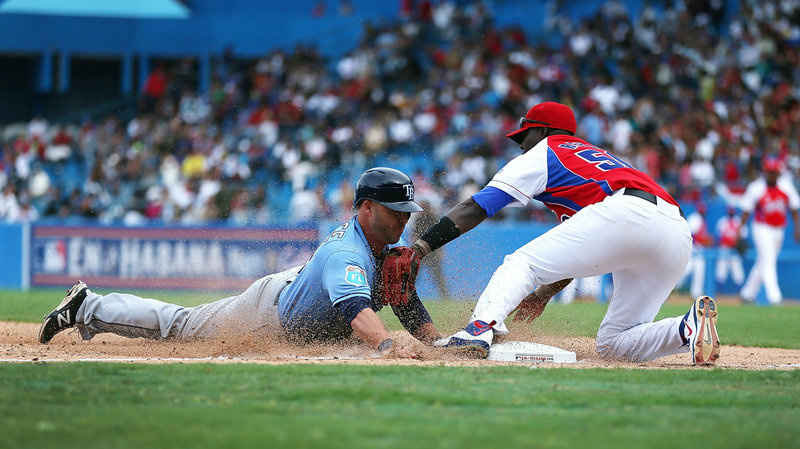 Tampa Bay Rays' Steve Pearce dives safely into third base during an exhibition game between the Cuban national team and the Tampa Bay Rays at the Estado Latinoamericano on March 22, 2016, in Havana, Cuba.