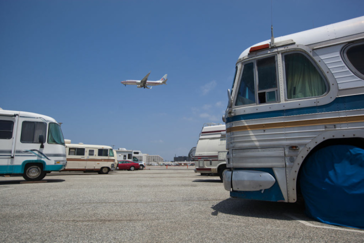 An airplane flies over the employee parking lot at Los Angeles International Airport. For pilots with short layovers, the lot provides a convenient, but noisy, place to sleep.