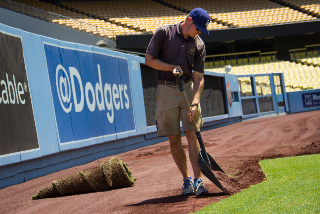 Groundskeeper Rod Sedlak shovels dirt to level out sod during the Dodger Stadium's transition into a soccer field for Saturday's Guinness International Champions Cup.