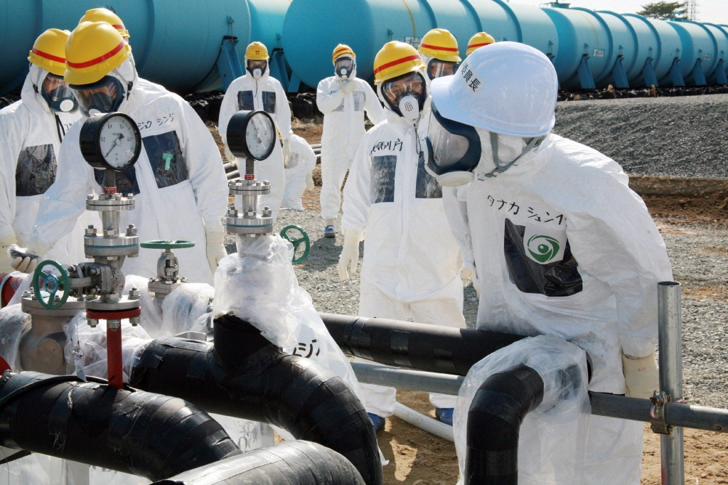 Nuclear Regulation Authority (NRA) Secretary General Shunichi Tanaka (R, w/white helmet) inspects the radioactive water-leaked plumbing with Tokyo Electric Power Co. (TEPCO) officials at the Fukushima Dai-Ichi nuclear power plant in Okuma in Fukushima prefecture, on April 13, 2013. (Photo by JIJI PRESS/AFP/Getty Images)