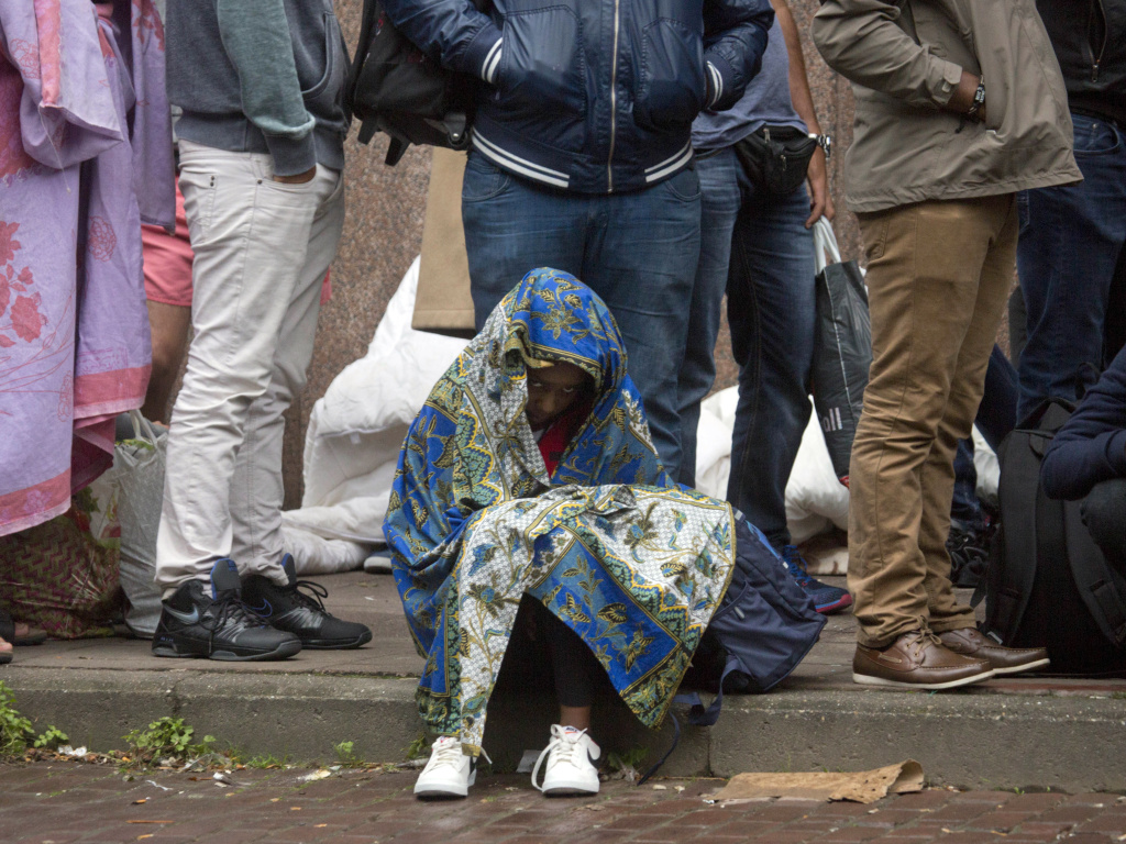 In this Sept. 1, 2015, file photo, a child waits in line at a migrant reception center in Brussels. Belgian migration minister Theo Francken said on Thursday he wants no part of a United Nations pact on safe and orderly migration, an international deal that has pushed Belgium's government to the brink of collapse.