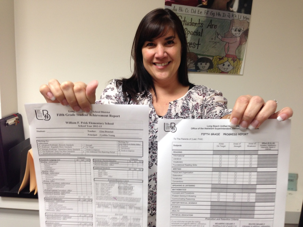 Long Beach fifth grade teacher Gina Bonetati holds her old report card, left, and the new transitional report card issued by her district.